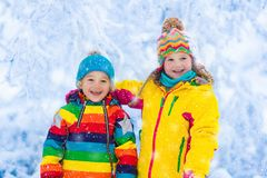 Kids play with snow in winter park Stock Photo