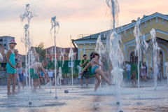 Children play and splash in the city`s fountains in the square. Editorial. 08.03.2017. Children play and splash in the city`s fountains in the square. Ukraine stock image