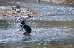 Children play splashing water in the natural creek. royalty free stock photos