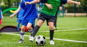 Children play sports. Kids kicking football match. Young boys playing soccer on the green grass pitch. Youth sports competiton. Horizontal soccer background stock images