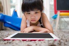 Children play Tablet on Living room carpet Royalty Free Stock Image