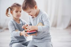 Children play with a toy designer on the floor of the children`s room. Two kids playing with colorful blocks. Kindergarten educational games royalty free stock images