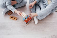 Children play with a toy designer on the floor of the children`s room. Two kids playing with colorful blocks. Kindergarten educational games. Close up view royalty free stock photos