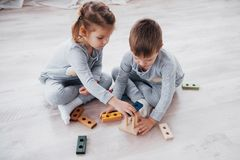 Children play with a toy designer on the floor of the children`s room. Two kids playing with colorful blocks. Kindergarten educational games stock photos