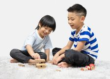 Children play with a toy designer on the floor of the children`s room. Two kids playing with colorful blocks. stock photo