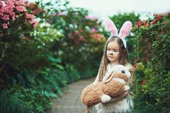 Children play with toy rabbit. Laughing child at Easter egg hunt with pet bunny. Little toddler girl playing with animal in the ga stock image