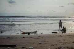 Children play with trash on the beach. ecologig worldwide problem, plastic on the beach royalty free stock image