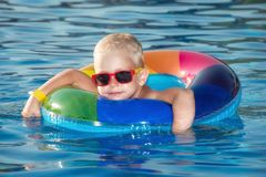 Happy little boy playing with colorful inflatable ring in outdoor swimming pool on hot summer day. Kids learn to swim. Child water stock photography