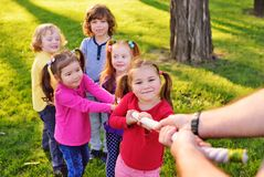 Children play tug of war in the park. royalty free stock photography