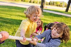 Children play tug of war in the park. royalty free stock images