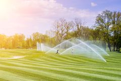 Children play under the streams of watering station golf courses stock photo
