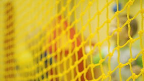 Children play volleyball. Yellow mesh closeup stock footage