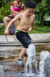Children play in the water fountain Stock Image