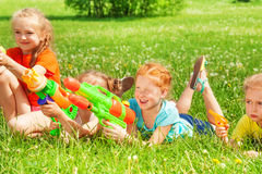 Children play with water guns on a meadow Stock Photos