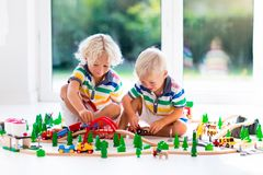 Children play wiht toy train. Kids wooden railway. Kids play with toy train railway. Children playing with wooden trains. Toys for little boy. Two brothers Royalty Free Stock Photography