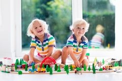 Children play wiht toy train. Kids wooden railway. Kids play with toy train railway. Children playing with wooden trains. Toys for little boy. Two brothers Stock Photos
