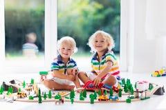 Children play wiht toy train. Kids wooden railway. Stock Image
