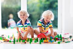 Children play wiht toy train. Kids wooden railway. Kids play with toy train railway. Children playing with wooden trains. Toys for little boy. Two brothers Stock Photography