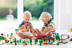 Children play wiht toy train. Kids wooden railway. Kids play with toy train railway. Children playing with wooden trains. Toys for little boy. Two brothers Stock Images