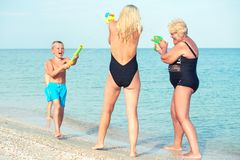 Free Children Play With My Mother And Grandmother With Water Pistols On The Beach.Summer Time Stock Images - 138452534