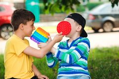 Free Children Play With Pop It Popular Toy. Happy Kids Having Fun Outdoors. Modern Antistress Toy For Children Stock Photo - 219870870