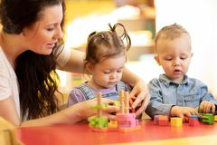 Free Children Play With Shapes And Colorful Wooden Puzzle In A Montessori Classroom Stock Photo - 144918870