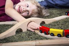 Child boy play with wooden train, build toy railroad at home or. Children play with wooden toy, build toy railroad at home or daycare. Toddler boy play with Royalty Free Stock Images