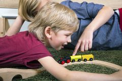 Brothers play with wooden train, build toy railroad at home or d royalty free stock image