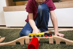 Child boy play with wooden train, build toy railroad at home or. Children play with wooden toy, build toy railroad at home or daycare. Toddler boy play with Stock Image