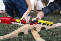 Brothers play with wooden train, build toy railroad at home or d stock photo