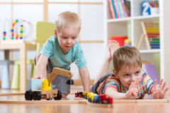 Children play with wooden train and build toy railroad at home, kindergarten or daycare Stock Photo