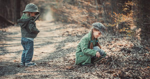 Children play in the woods. Small children play in the woods, photo in vintage style Stock Images
