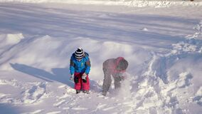 Children played in the snow. Children throw soft white snow high up. two brothers standing on white snow together throw snow on top of their heads stock video