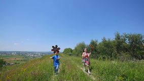 Children are played with a wind turbine. Children colorful pinwheel spinning in the wind. Against the background of stock footage
