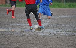 Children players during a football match in a playing field full
