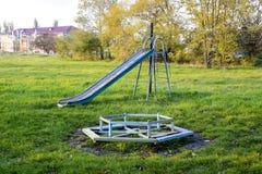 2 children playground 摇摆和滑的幻灯片 免版税图库摄影