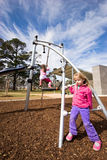 Children at playground. Two children on playground equipment with cloudy skies royalty free stock photo