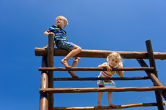 Children at the playground. Two young children sitting at the top of playground equipment stock photography