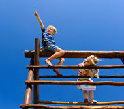 Children at the playground. Two young children sitting at the top of playground equipment royalty free stock photos