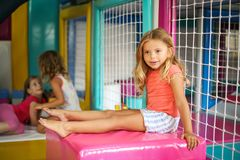 Children in playground. Little girl sitting in playroom and looking away stock photos