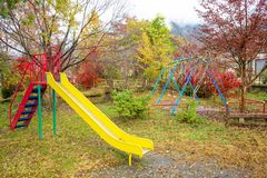 Children playground in autumn park. Children playground with fall foliage colors in autumn park. slide and swing for Preschool or kindergarten yard. Daycare for stock images