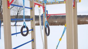 Children playground gymnastic rings swing, snow landscape a winter Stock Photography