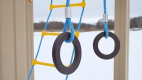 Children playground gymnastic rings swing, snow winter landscape a Stock Images