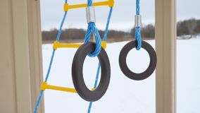 Children playground gymnastic rings swing, snow winter landscape a. Children playground gymnastic rings swing, snow winter landscape Stock Photo
