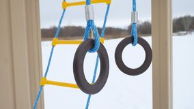 Children playground gymnastic rings swing, snow winter landscape a Stock Photo
