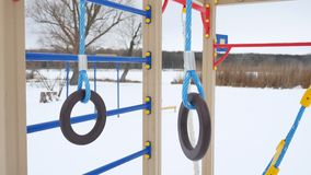 Children playground gymnastic rings swing, winter snow landscape Royalty Free Stock Photo