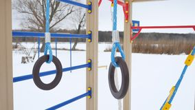 Children playground gymnastic rings swing, winter snow landscape Royalty Free Stock Image