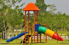 Children playground near the houses. Colorful kid`s playground which consists of slides, swings, and others for kid`s enjoyment and play Stock Photo