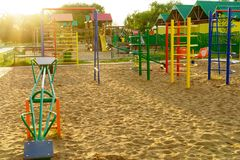 Children playground in a park. Modern colorful children playground in a park in rays of the sun royalty free stock images