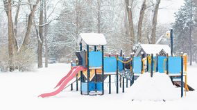 Children playground in a public park in winter. It is snowing. There are trees and naked tree branches covered with snow in the background Stock Photography